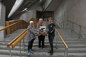 Gillain Semple (left) with Christine Grahame (centre) and her son Rory Semple as she became the five millionth visitor to the Scottish Parliament since the building opened in 2004. Picture: Andrew Cowan