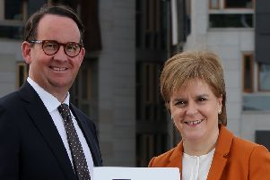 First Minister Nicola Sturgeon receives the Sustainable Growth Commission report from commission chair Andrew Wilson last year.