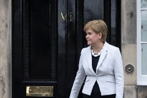 Scotland's First Minister Nicola Sturgeon outside the front door to Bute House in Edinburgh.