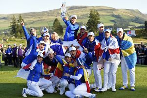 European captain Catriona Matthew holds the Solheim Cup aloft as she is lifted up by her team after their dramatic last-hole victory over Team USA at Gleneagles. Picture: Ian Rutherford/PA