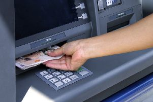 A person takes out cash from an ATM