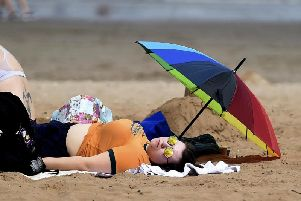 A beach goer catches some rays in Portobello this summer