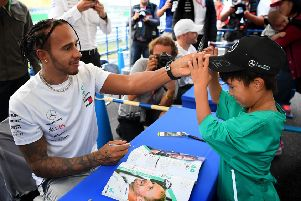Lewis Hamilton with a young fan at an autograph signing session ahead of the F1 Grand Prix of Japan at Suzuka. Picture: Clive Mason/Getty