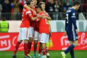 Aleksandr Golovin celebrates with teammates after scoring the fourth Russian goal as a dejected Andrew Robertson walks past.