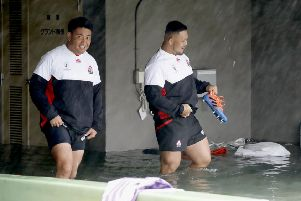 Japan players Takuya Kitade, left, and Yusuke Kizu wade through a flooded walkway at a stadium in Tokyo as the team try to train for the Scotland match. Picture: Yuki Sato/Kyodo News via AP