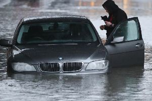 A man with car in a flooded Sheffield street after torrential rain in the area. Picture: Danny Lawson/PA Wire
