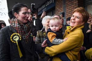 Scottish Nationalist Party (SNP) leader Nicola Sturgeon (R) holds a baby as she campaigns with SNP candidate Catriona MacDonald on November 12, 2019 in Edinburgh. (Photo by ANDY BUCHANAN/AFP via Getty Images)