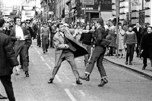 A youth slashes the coat of Special Branch police officer George Johnston with an open razor during a pro-IRA march through Glasgow's Renfield Street in 1971 (Picture: Allan Milligan)