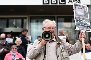 A licence fee protester outside the BBC at Pacific Quay