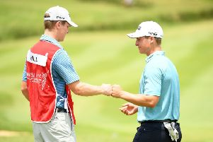 Calum Hill celebrates holing a birdie putt at the last in the second round of the AfrAsia Bank Mauritius Open with his caddie and brother, Ian. Picture: Getty Images