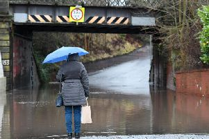 A woman surveys flooding in East Kilbride