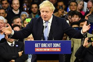 Boris Johnson on a podium with his campaign slogan of 'Get Brexit Done'. Picture: PA