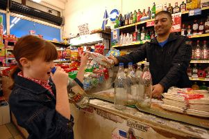 A young girl returns glass bottles to her local shop and gets cash in return