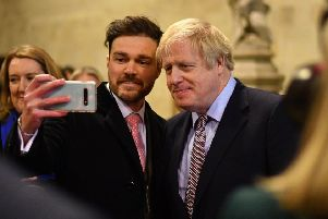 Boris Johnson poses for a selfie as he greets newly elected Conservative MPs in the Palace of Westminster (Picture: Leon Neal/pool/AFP via Getty Images)