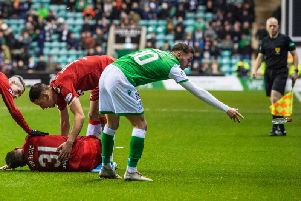 Martin Boyle removes the vodka bottle from the pitch as Rangers defender Borna Barisic lies injured on the surface. Picture: SNS