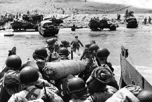 American assault troops and equipment land on Omaha beach in 1944. Picture: Fox Photos/Hulton Archive/Getty Images