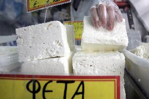A shop assistant lifts a slub of feta cheese in Athens (Picture: Aris Messinis/AFP/Getty Images)