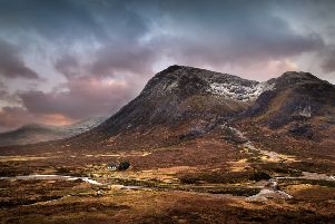 A small house nestles in the valley beneath a snow capped mountain in Glencoe.