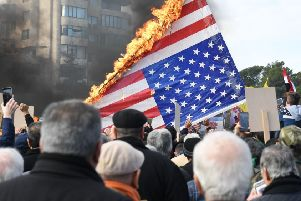 Syrian demonstrators burn the US flag as they gather in the northern Syrian city of Aleppo to mourn the death of Iranian military commander Qasem Soleimani and nine others in a US air strike in Baghdad. (Picture: AFP via Getty Images)