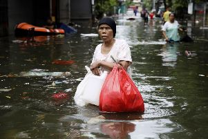 A woman wades through floodwater in Jakarta, Indonesia, where dozens of people have died. (Picture: Dita Alangkara/AP)