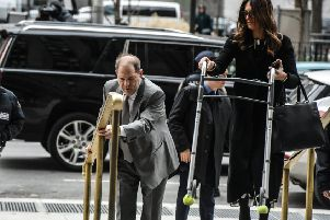 Harvey Weinstein's lawyer Donna Rotunno carries his walker up a flight of stairs as he arrives at the New York City criminal court for his sex crimes trial (Picture: Stephanie Keith/Getty Images)