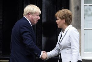 Boris Johnson and Nicola Sturgeon shake hands but relations do not appear overly friendly