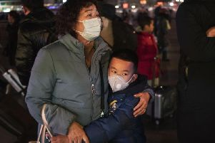A Chinese boy hugs a relative as she leaves to board a train at Beijing Railway station. Travel in Wuhan, where coronavirus has broken out, has been severely restricted. Picture: Kevin Frayer / Getty Images