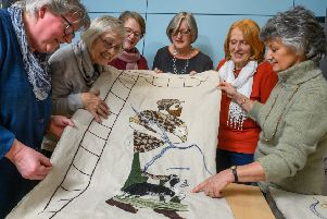 Stitchers with one of the welcome panels in Hawick.