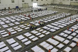 Workers arrange beds in a convention center that has been converted into a temporary hospital in Wuhan in central China's Hubei Province,