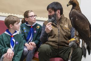 Handler Douggie McKenna holds Kasia the golden eagle as cubs Moya McLaughlin and Innes Reilly look on.