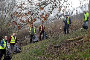 The group of volunteers who look after the gardens of Old Gala House pick litter along the steep banking at Huddersfield Street in Galashiels.