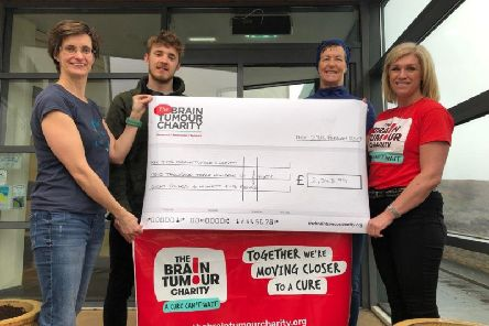 Louise Scott and two of her fellow swimmers present a cheque fo The Brain Tumour Charity.