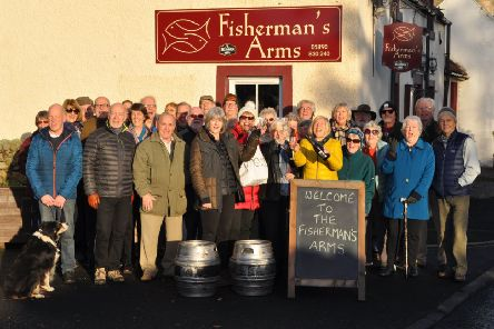 New Fisherman's Arms landlady Karen Miller (fourth from left) is welcomed to Birgham by villagers with some celebration bubbly