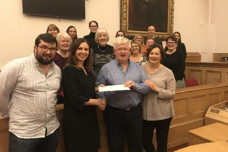 Retiring procurator fiscal Graham Fraser receives a cookery school voucher from assistant procurator fiscal Alison Michie, based at the Crown Office in Edinburgh, watched by his family and procurator fiscal service staff at Jedburgh and Selkirk.