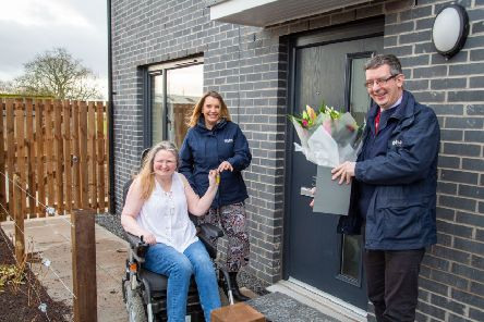 HA tenant Anita Green receives the keys to her new home at Millar Court in Duns from Housing Officer Katie Cockburn and also flowers from Development Manager Colin Young.