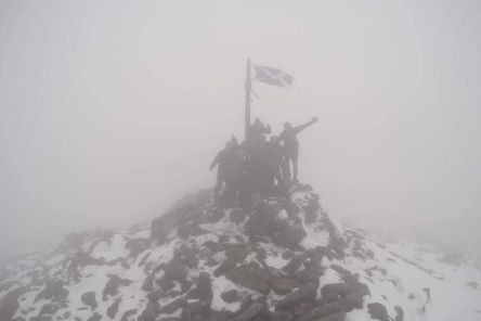 The caber-carriers celebrate in misty conditions at the summit of Mount Keen. Picture: Caber Walk 2019