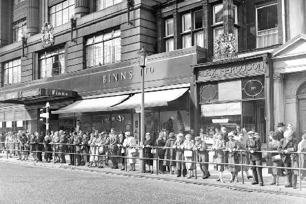 Traffic lights system  at West End  Edinburgh  - People watch new system from barrier in Princes Street.  Shops in the background are Binns and Alex Ferguson.