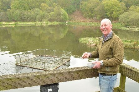 Bowden Spring owner Jim Gargaro gets ready to feed fish on the fly loch at his fishery on the A706 road above Linlithgow. Picture: Nigel Duncan