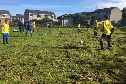Kids attempt to play football on a badly maintained pitch at Buckstone.