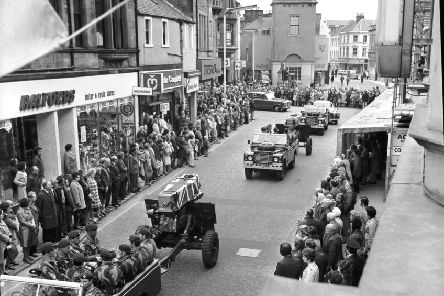 Pedestrians stop in silent tribute as the coffins of two part-time paratroopers killed in the River Trent disaster are carried through Falkirk High Street in October 1975.