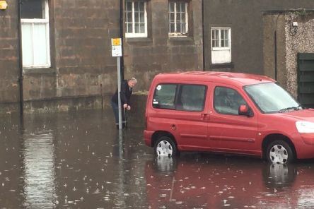 A man measures the depth of the floods at the Prom.