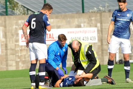 Raith captain Kyle Benedictus shows concern for Ross Matthews as he gets attention from sports therapist Iain Williamson and the East Fife club doctor - credit- Fife Photo Agency