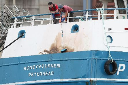 Crew members of the Peterhead-registered Honeybourne III clean off marks from the stern of the vessel