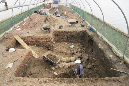 Digging in a polytunnel in 34 degree heat, the medieval ditch is revealed along with the 16th century path, just behind the man in the hardhat in the foreground.