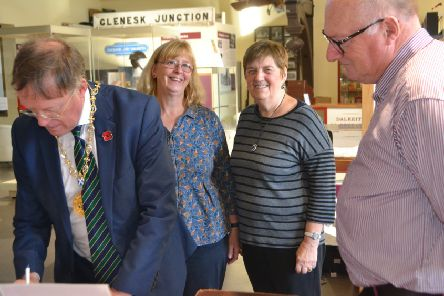 Provost Peter Smaill signs the visitors' book at Dalkeith Museum as volunteers Helen Gordon, Norma McNeill and Norman Brett look on.