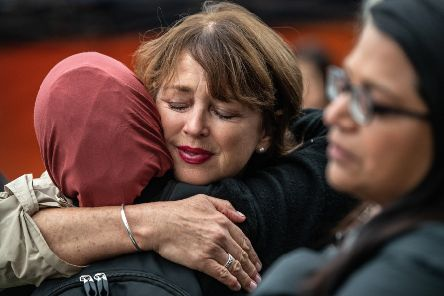 Women hug to comfort each other next to flowers and tributes laid by the wall of the Botanic Gardens on March 17, 2019 in Christchurch, New Zealand. Picture: Carl Court/Getty Images