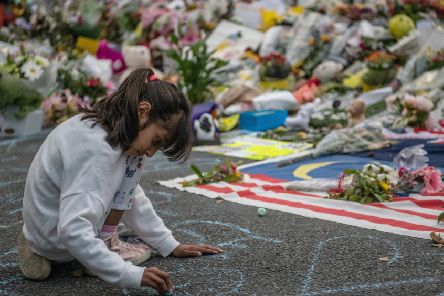 A young girl writes a message in chalk next to flowers near Al Noor mosque in Christchurch (Picture: Carl Court/Getty)