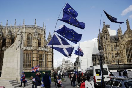 Pro-EU campaigners outside Westminster fly EU and Scottish flags. Picture: AP/Matt Dunham