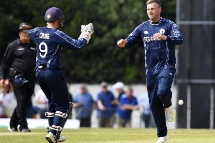 Mark Watt, right, celebrates a wicket against England with Matthew Cross. Picture: SNS Group