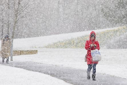 Commuters make their way through April snow showers today in Livingston, West Lothian